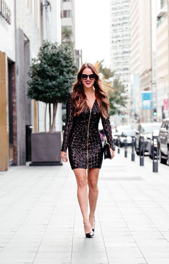 black sequin geometric mini dress with a zipper on the front, black heels and a clutch