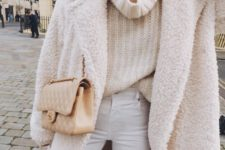 12 white jeans, an oversized chunky knit turtleneck sweater, a creamy teddy coat and a neutral bag