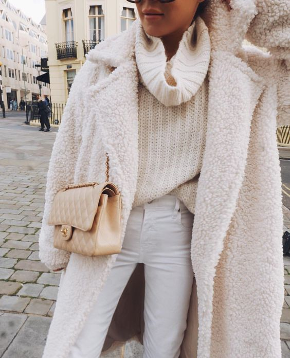 white jeans, an oversized chunky knit turtleneck sweater, a creamy teddy coat and a neutral bag