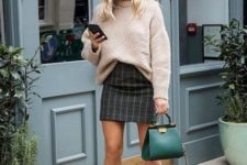 13 a blush oversized sweater tucked in a dark plaid mini skirt, creamy boots, an emerald bag
