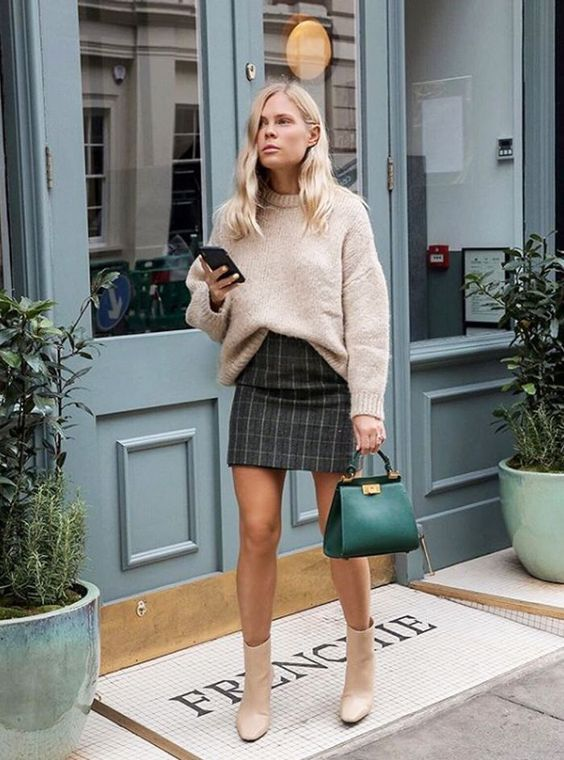 a blush oversized sweater tucked in a dark plaid mini skirt, creamy boots, an emerald bag