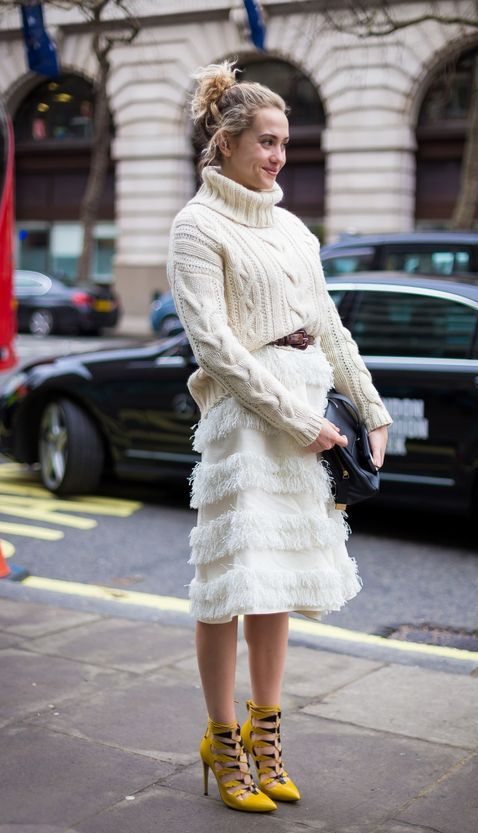 a whimsy outfit of a creamy cable knit sweater, a feathered knee skirt, bright yellow lace up shoes