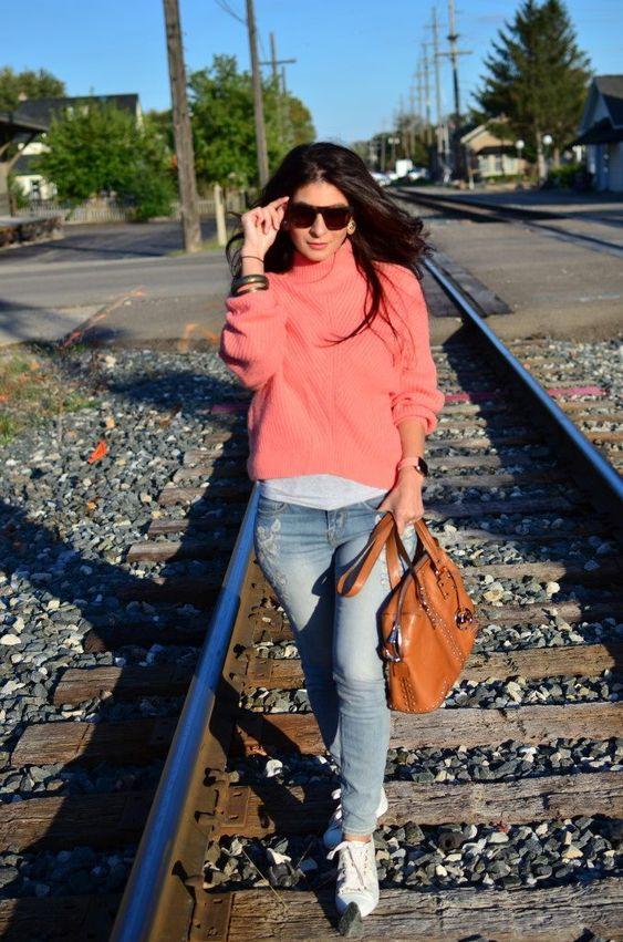 a white tee, c roal pink sweater, blue jeans, white sneakers and a cognac-colored bag