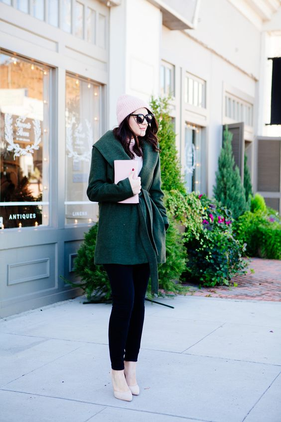 black jeans, an emerald coat, nude heels, a blush beanie and a clutch for a festive look