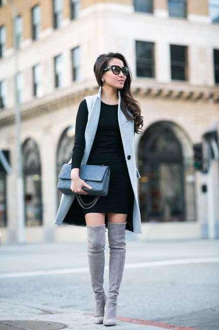 grey tall boots, a black mini dress with long sleeves, a grey long waistcoat and a grey bag