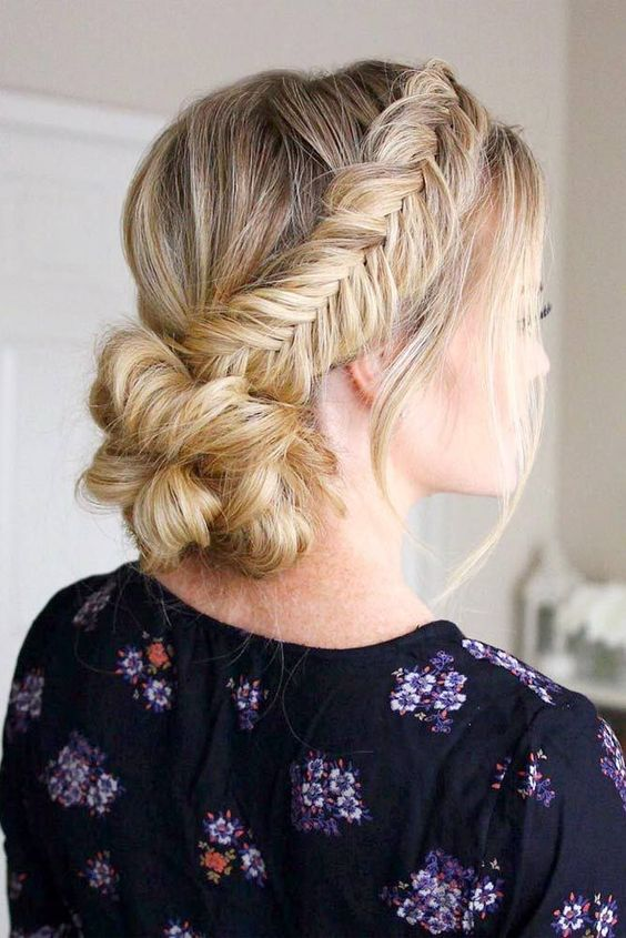 a low bun with two fishtail side braids and a bump is a chic and comfy to wear option