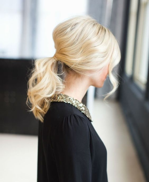 a messy wavy low ponytail with a bump and some bangs is a cool DIY idea