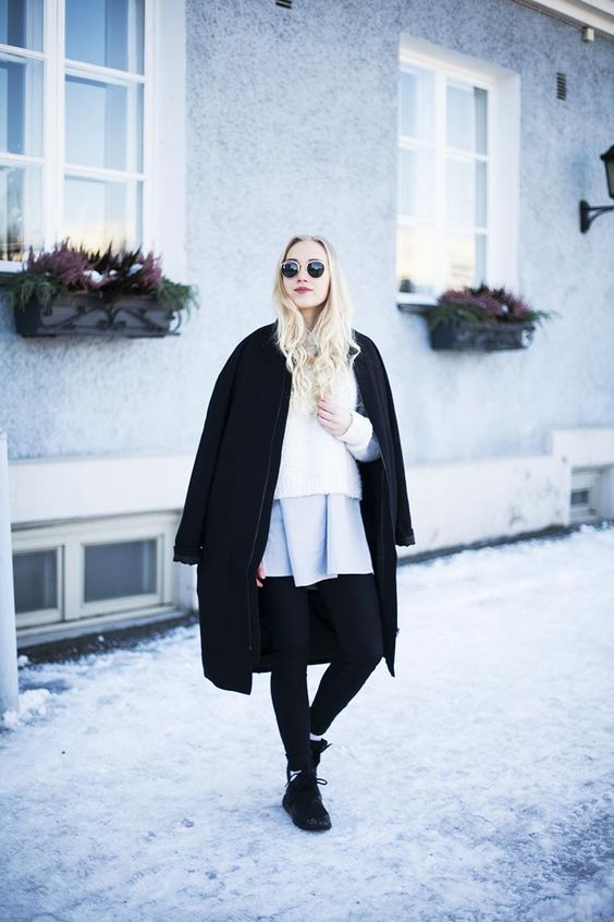 a white sweater, a grey pleated mini, black boots, a black coat is a stylish statement