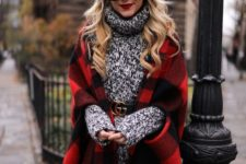14 black skinnies, a long sweater with a logo belt and a plaid cape as a trendy touch to the outfit