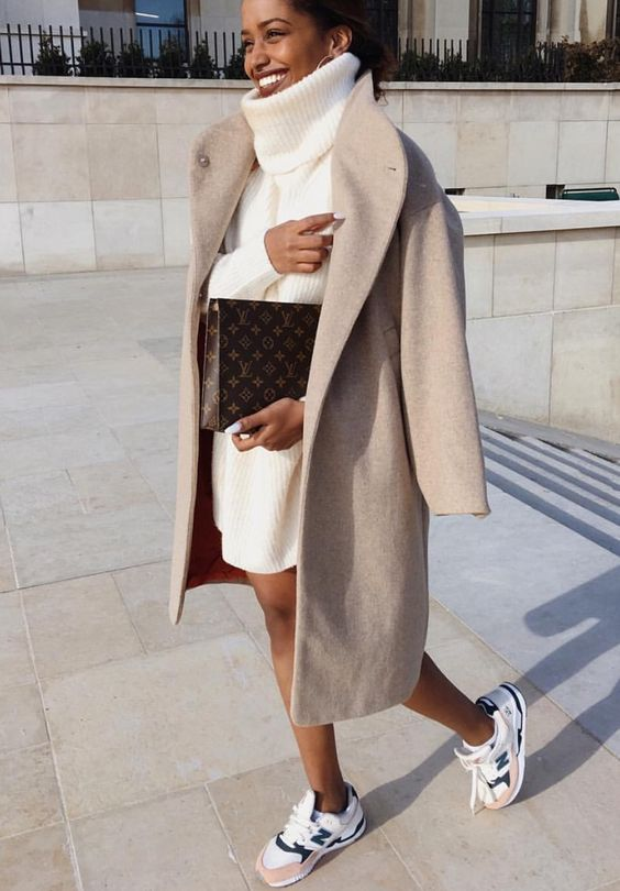 a creamy oversized turtleneck sweater dress, sneakers and a midi camel coat plus a printed clutch