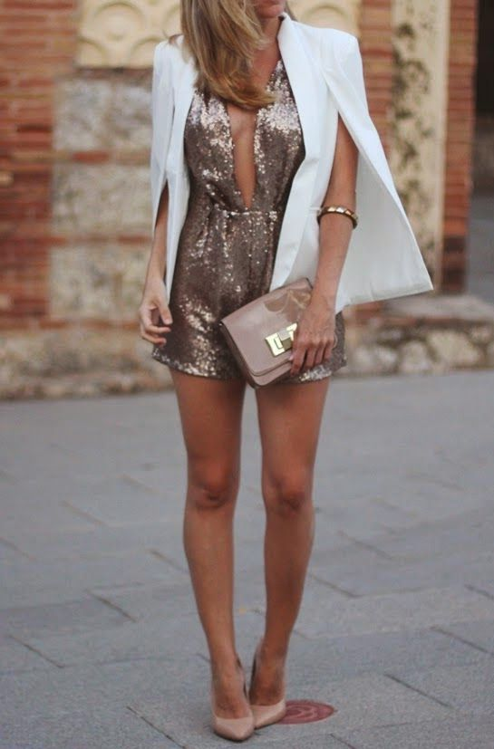 a rose gold romper with a plunging neckline, nude heels, a matching clutch and a white cape