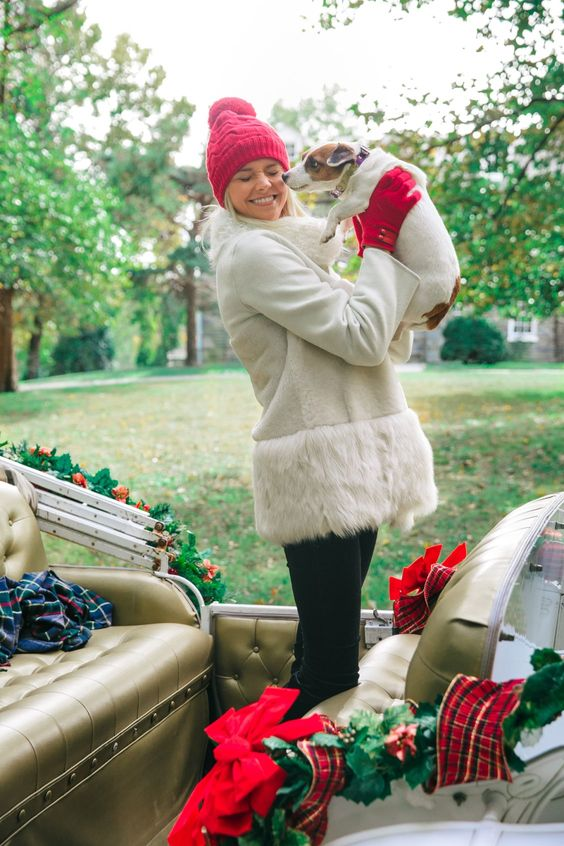 black skinnies, a white shearlign coat with fur, a red pompom beanie and red gloves