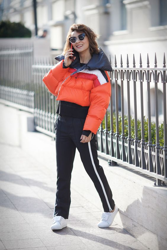 striped sporty pants, white sneakers, a coral striped cropped puffer jacket for a sport chic winter look