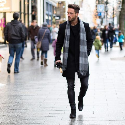 Black shirt, black coat, dark colored jeans and gray striped scarf