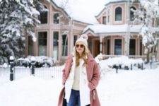 With beige sweater, jeans, pale pink coat and pom pom hat