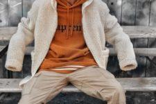 With beige teddy bear coat, orange beanie hat, beige pants and sneakers