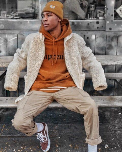 With beige teddy bear coat, orange beanie hat, beige pants and sneakers