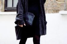 With black dress, cardigan and velvet clutch