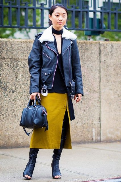 With black shirt, black jacket with white fur collar, black bag and cutout boots