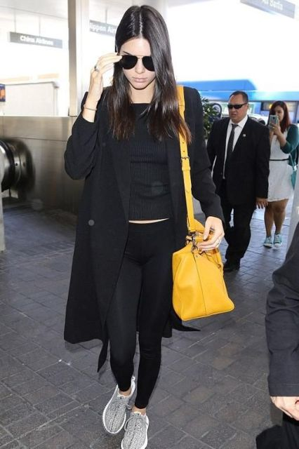 With black shirt, black leggings, black coat and yellow bag