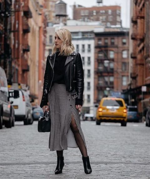 With black turtleneck, black leather jacket, small bag and ankle boots