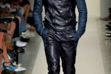 With blue shirt, black leather vest and brown boots