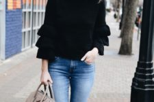 With distressed jeans and beige bag