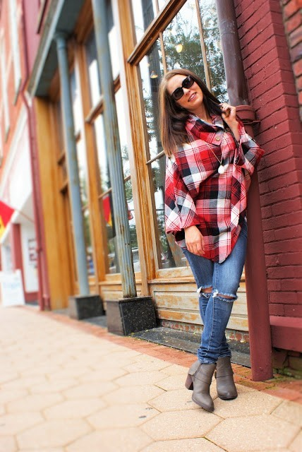With distressed jeans and gray leather boots