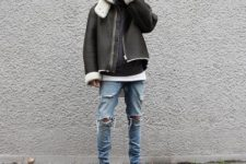 With distressed jeans, gray sneakers and shearling coat