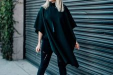 With emerald cape, skinny pants and sunglasses