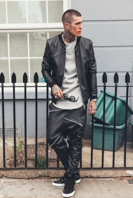 With gray long shirt, black leather jacket and sneakers