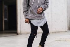 With gray long t-shirt, black distressed pants and beige boots