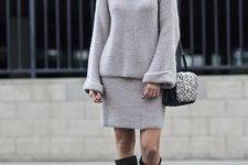 With gray skirt, black high boots and fur bag