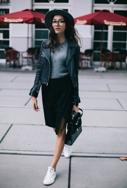 With gray sweatshirt, wide brim hat, leather jacket, white sneakers and black bag