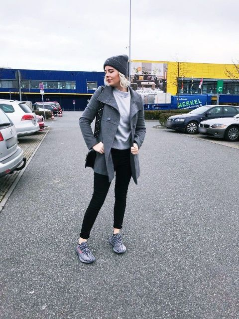 With light gray sweatshirt, gray beanie hat, black pants, black bag and gray coat