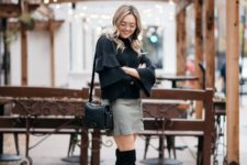 With mini skirt, black bag and black over the knee boots