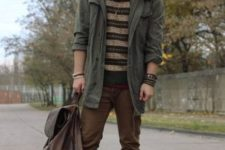 With olive green jacket, brown pants, lace up boots, backpack and knitted scarf