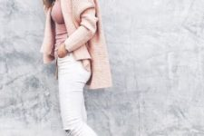 With pale pink shirt, pale pink sweater and white distressed pants