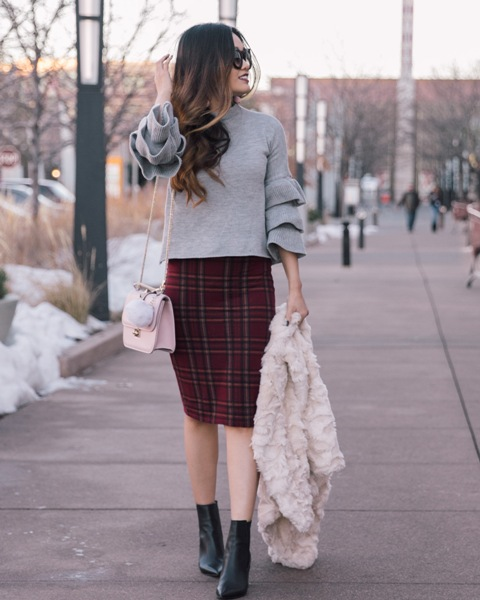 With plaid skirt, pastel colored bag, black ankle boots and fur jacket