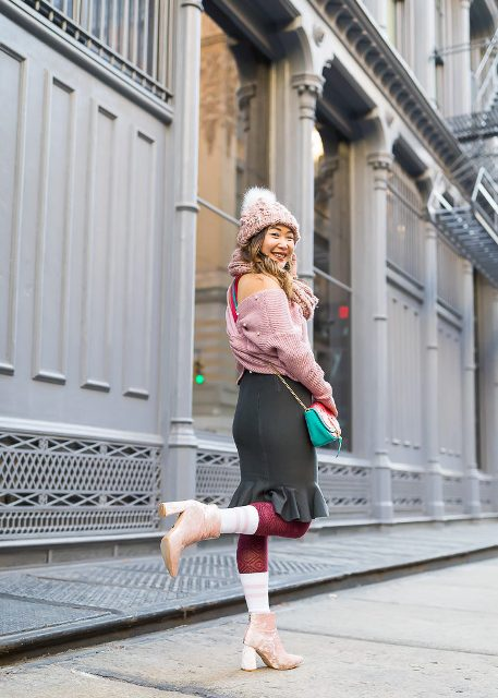 With pom pom hat, ruffled skirt, colorful bag and pale pink boots