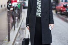 With printed shirt, black beanie, gray coat, flat shoes and small bag