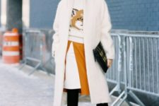 With printed sweater, white coat, black clutch, black tights and black ankle boots