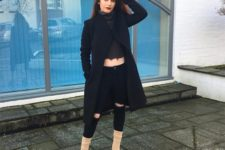 With top, distressed pants and black coat