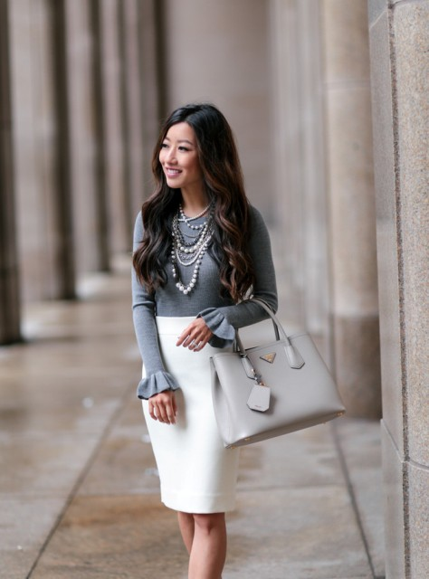 With white pencil skirt and light gray bag