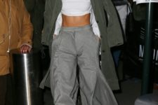 With white shirt, gray wide leg trousers and olive green coat