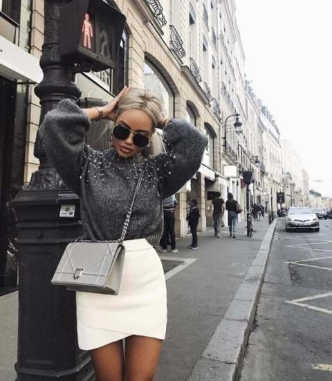 With white wrapped skirt and gray bag