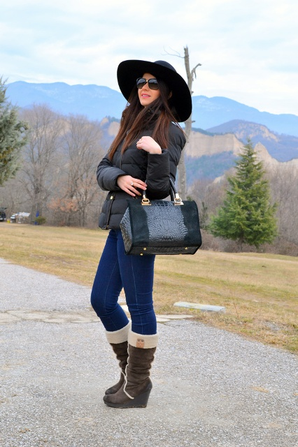 With wide brim hat, jeans, black puffer jacket and bag