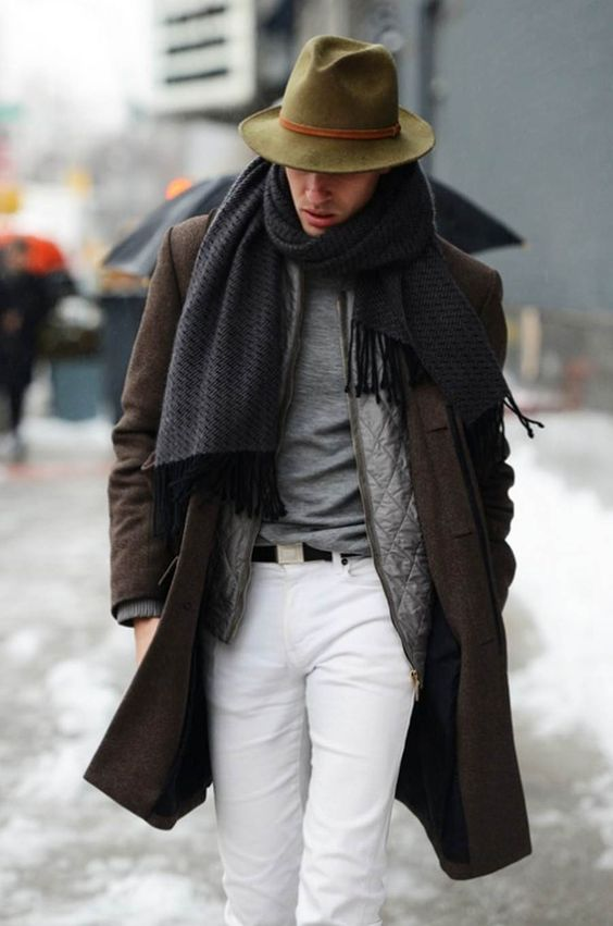 white jeans, a grey tee, a grey quilted vest, a brown coat, a grey scarf and a green hat