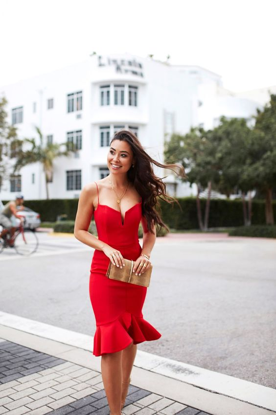 a jaw-dropping red dress with a deep neckline, a fittign silhouette, a ruffled skirt and a metallic clutch