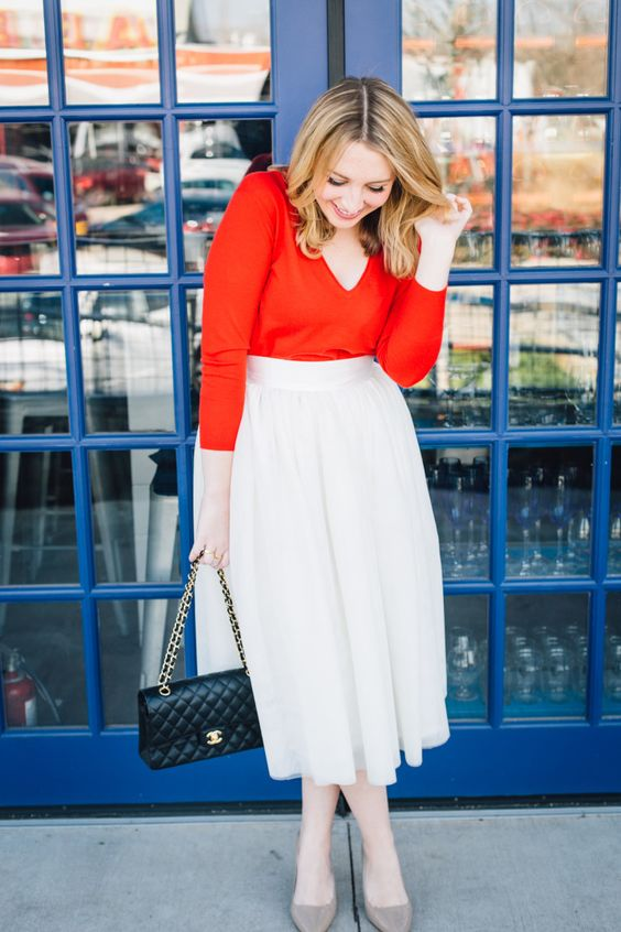 a red long sleeve top with a V-neckline, a neutral midi skirt, grey heels and a black bag